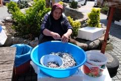 Eine Marktfrau nimmt die kleinen Fische aus