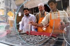 Die drei Herren machen Eis. Dazu wird die Eismasse in die silbernen Röhrchen gefüllt, welche in einen Eisblock gesteckt werden. Sobald alles gefrohren ist, ist das Eis fertig.
