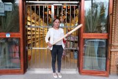 Die Verkäuferin des Haferflockenladens mit Knüppel vor ihrem Geschäft. Nicht gerade angsteinflösend, aber trotzdem irgendwie schräg