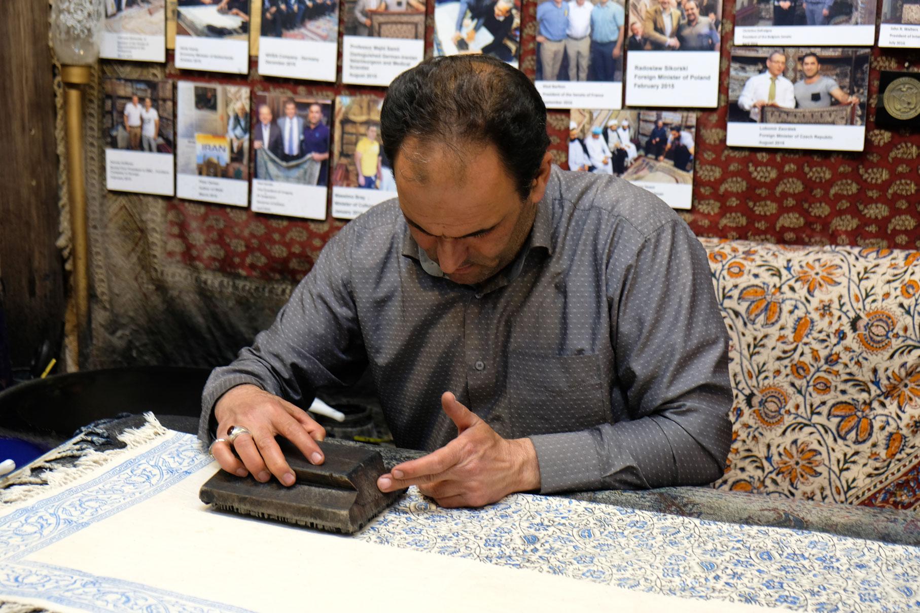 Mit alten Holzstempeln werden die Tücher von Hand bedruckt. Im Hintergrund sind die Fotos der Promis aufgehängt.