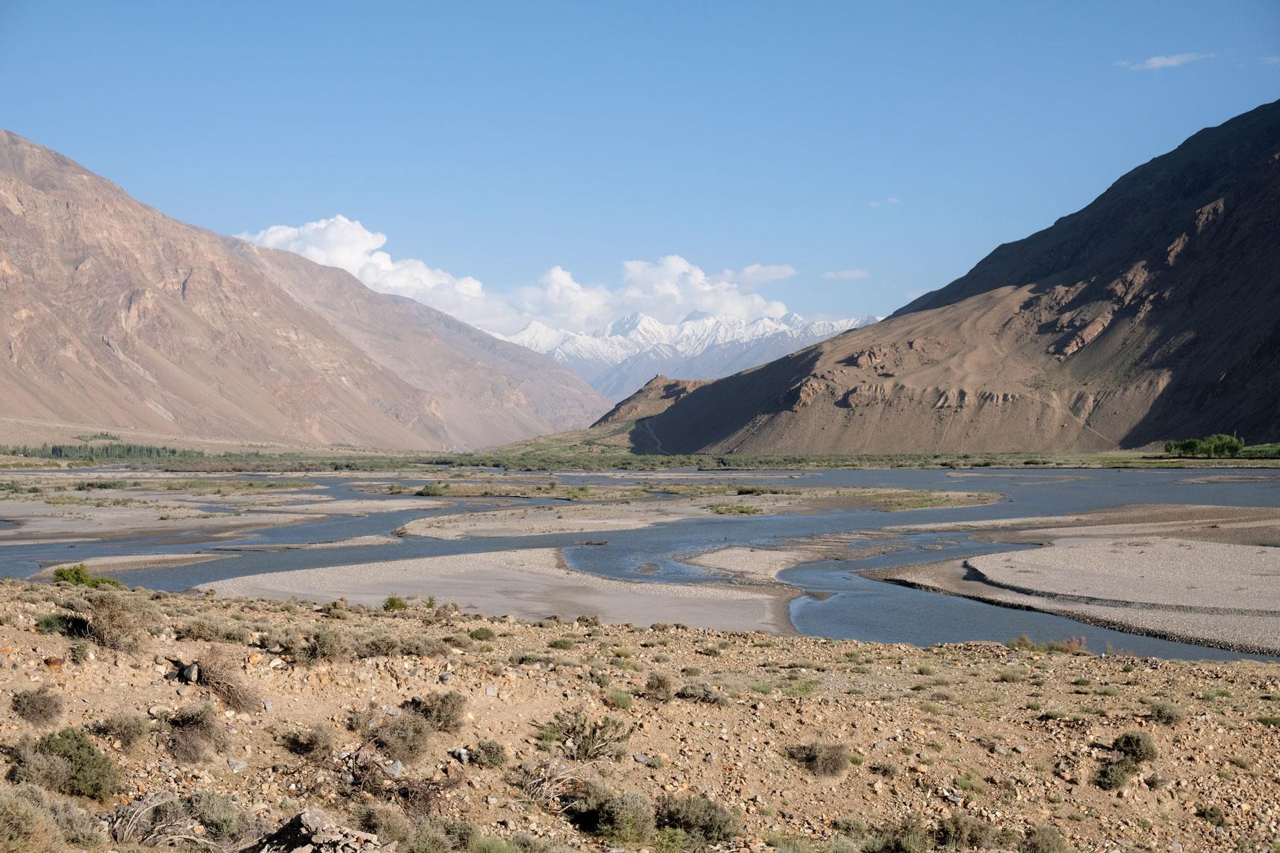 Je weiter wir nach Süden fahren, desto breiter wird der Panj. Am Horizont erscheint der Hindukusch.