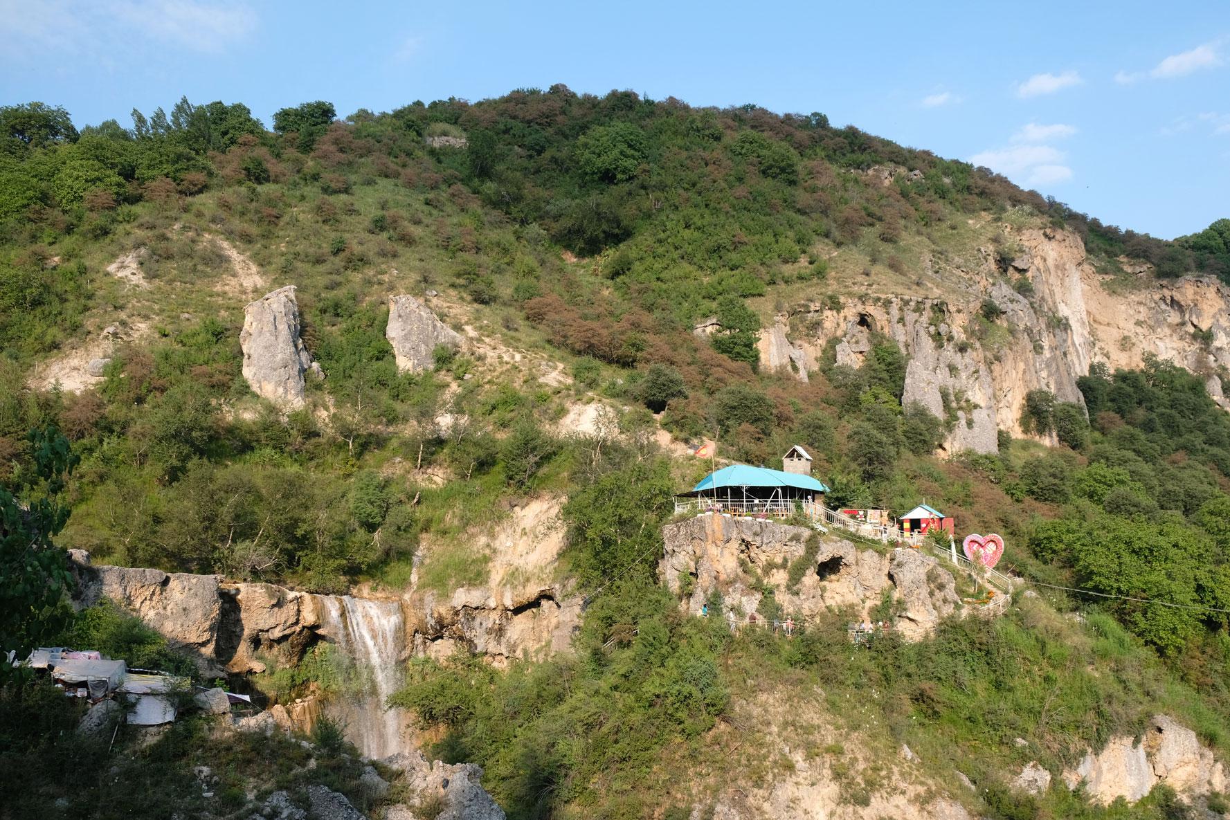 Zwischen den Ständen finden wri schließlich doch noch eine Lücke und können zum Wasserfall hinüberschauen