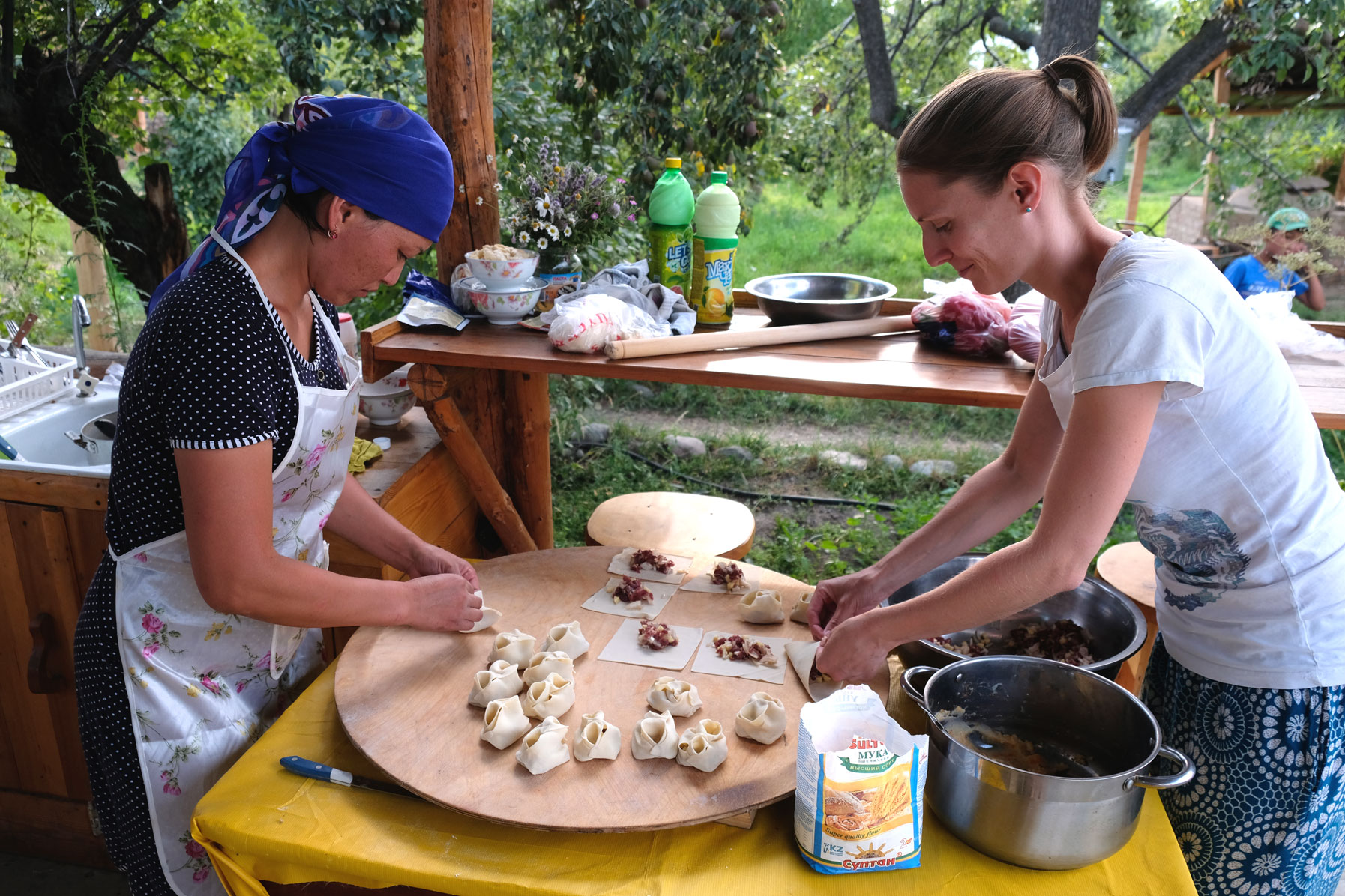 Auf dem ausgerollten und kleingeschnittenen Teig wird die Füllung mit einem Löffel verteilt. Anschließend werden die Teigstückchen kunstvoll geschlossen.