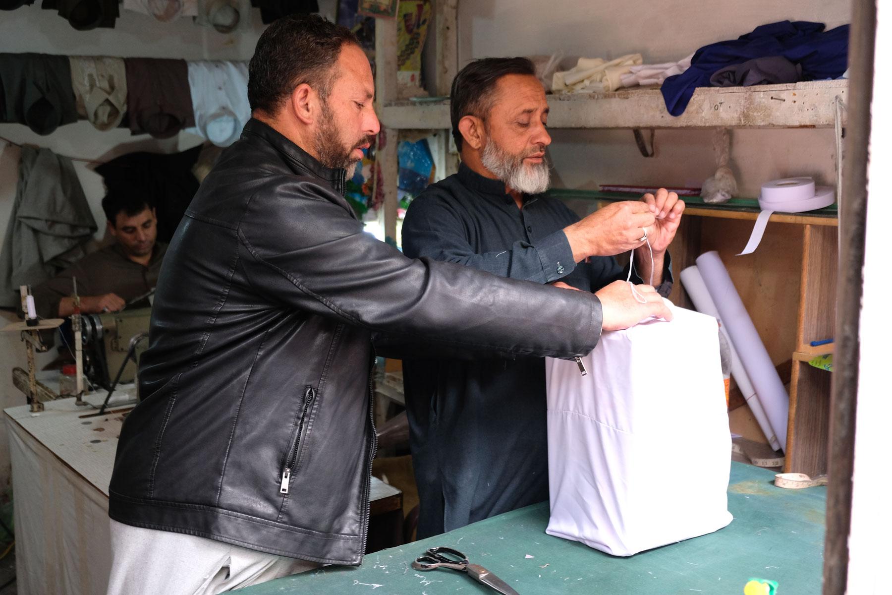 Das war uns ganz neu: Päckchen müssen in Pakistan in weißen Stoff eingenäht werden, bevor sie verschickt werden können. Sieht auf jeden Fall nett aus!