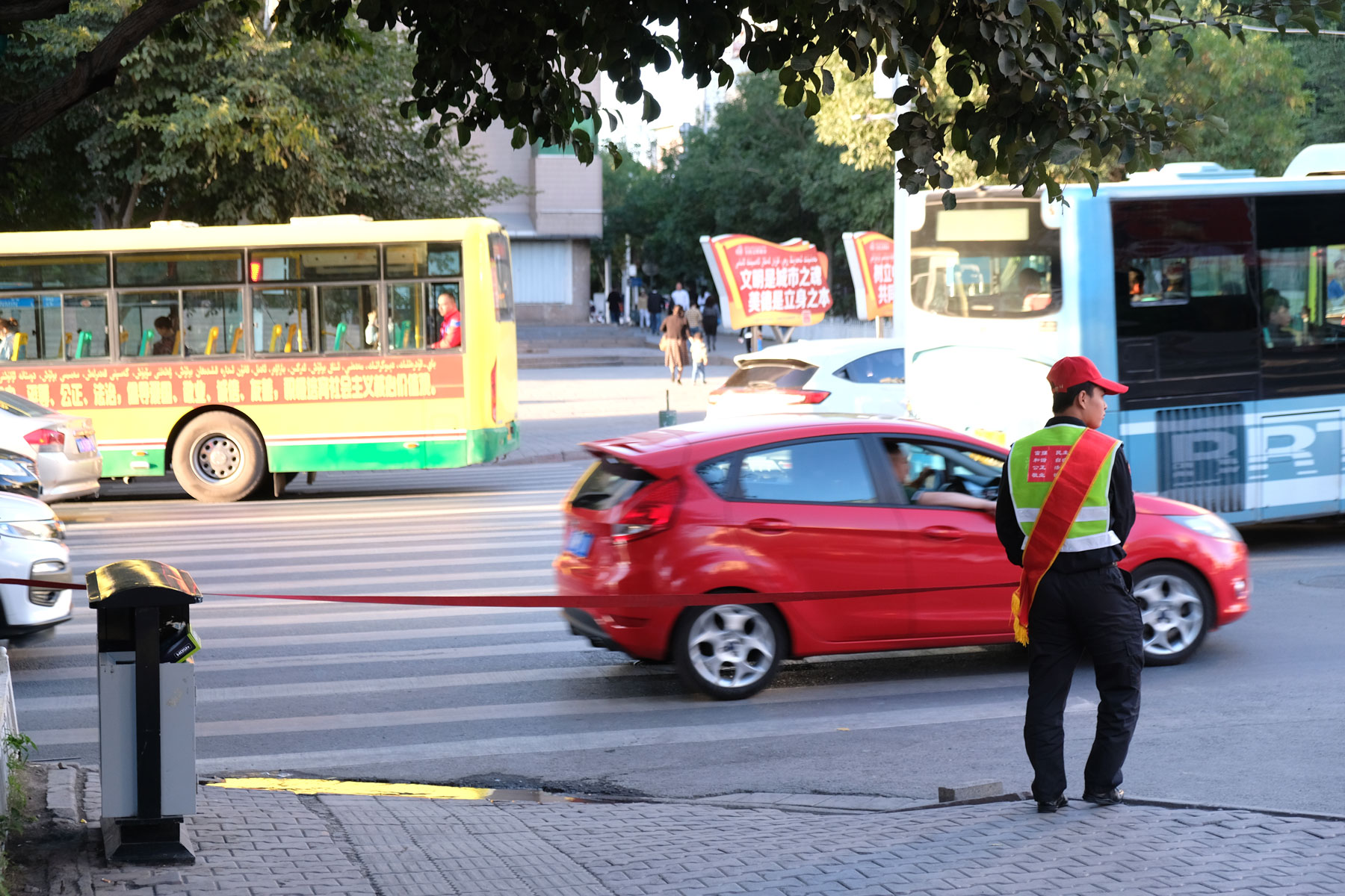 """Achtung, Achtung! Damit wirklich niemand über die rote Ampel läuft, finden wir in ganz Urumqi immer wieder """"Straßenwärter"""", die ein rotes Band halten. Erst, wenn die Ampel auf grün umschaltet, lassen sie das Band fallen und die Fußgänger dürfen die Straße überqueren."""