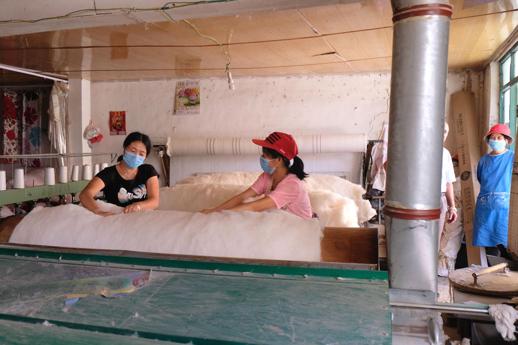 Zufällig stolpern wir in einen kleinen Raum, in dem zwei Frauen Baumwolle weiterverarbeiten