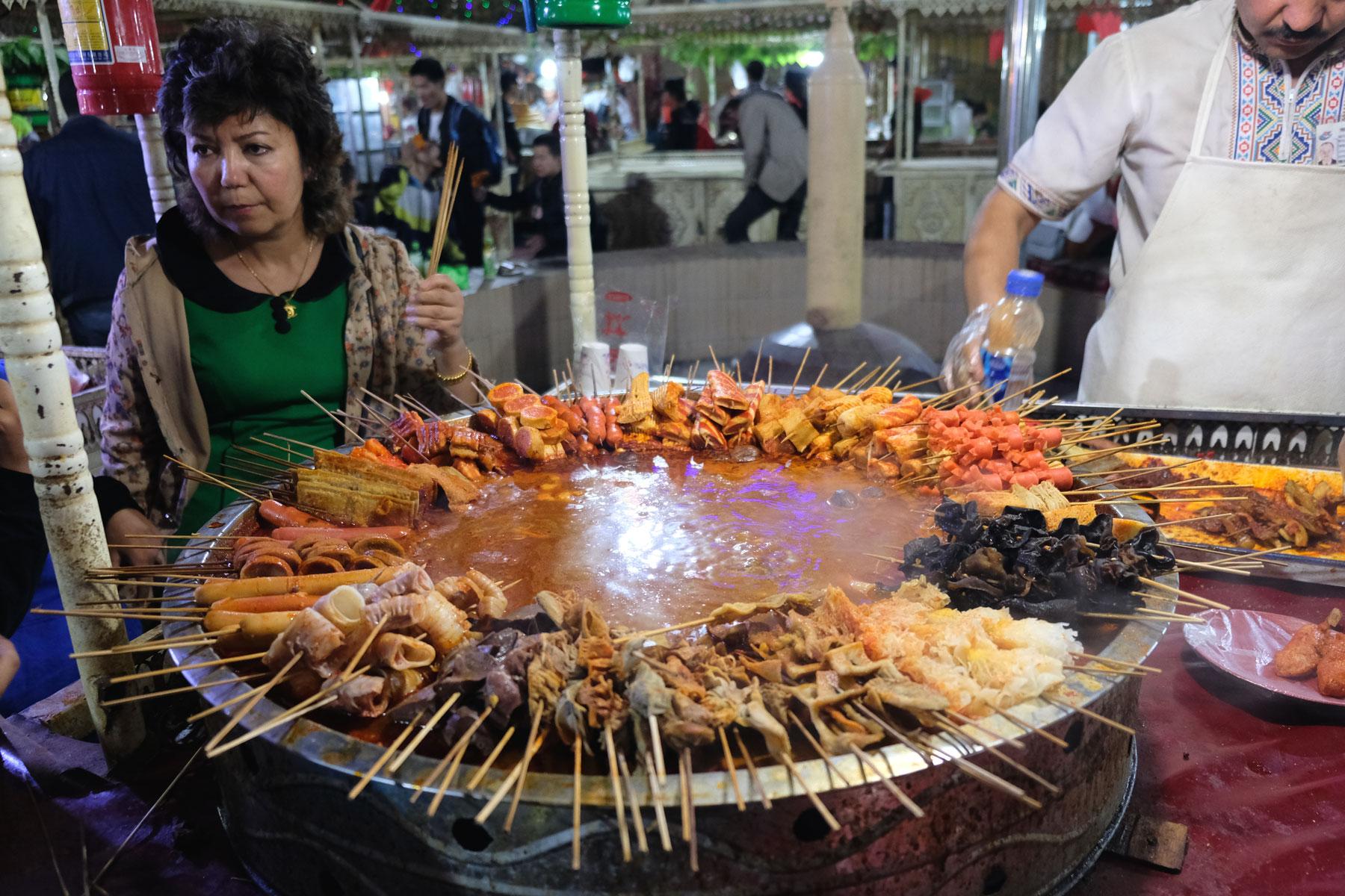 Das kulinarische Angebot am Nachmarkt wartet mit für uns exotischen Spießchen auf