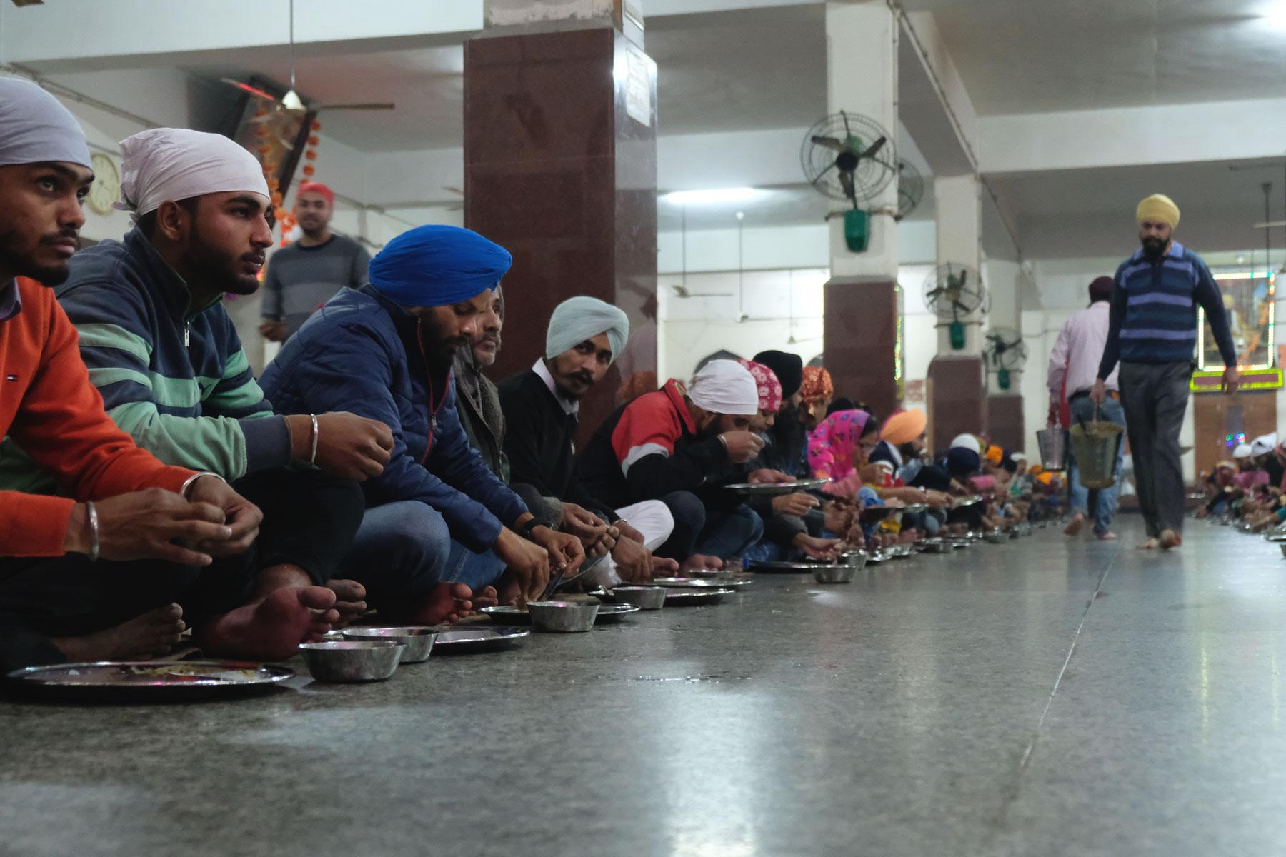 In langen Reihen sitzend nehmen die Tempel-Besucher ihr Essen zu sich
