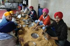 Eine Gruppe Freiwilliger poliert die bereits gespülten Teller in Sägemehl