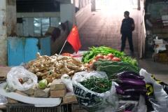 Chinesisches Gemüse, im Hintergrund ein Wachmann