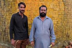 Zwei Arbeiter vor dem Schornstein der Fabrik, auf dem sich ein grellgelber Belag abgesetzt hat