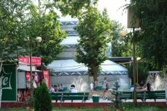 """Hinter den Bäumen versteckt blitzt die """"größte Jurte der Welt"""" (Zitat Reisehührer) hervor - sie hat drei Stockwerke"""