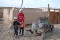 Zwei Kinder neben einem Motor, der schon bessere Tage gesehen hat