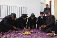 Auch die alten Herren nehmen auf dem Boden Platz und essen gemeinsam