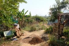 Blick auf die Farm und Haufen aus Sand und Erde, die die Freiwilligen in kleine Plastiksäckchen abfüllen müssen