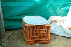 Auf einem Brotkorb sitzend, wird die Notdurft in einen Eimer verrichtet und anschließend mit Sägespänen bedeckt. Pinkeln ist allerdings nicht erlaubt und muss außerhalb im Gebüsch erledigt werden.