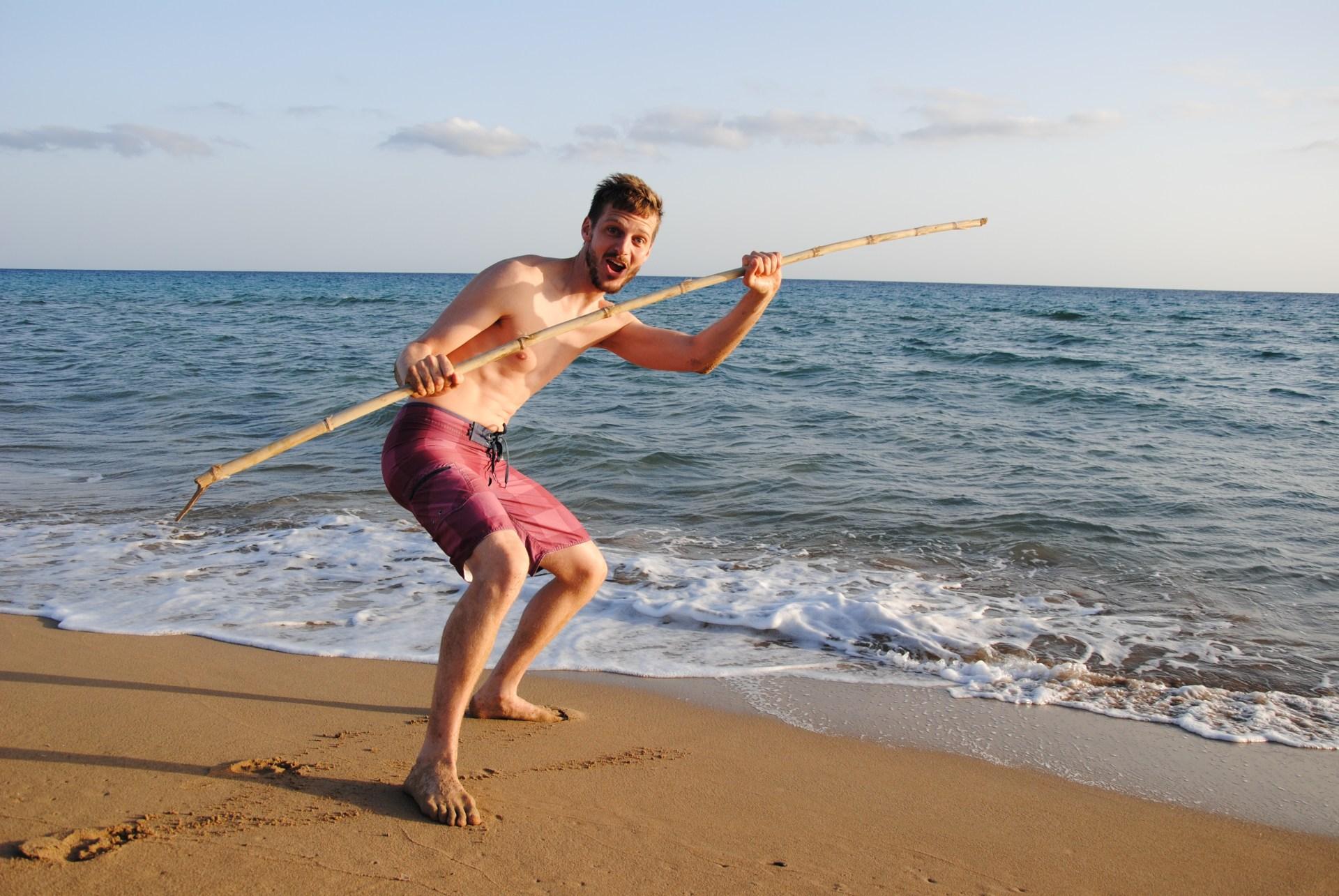 Sebastian steht am Strand und hat einen langen Stock in der Hand