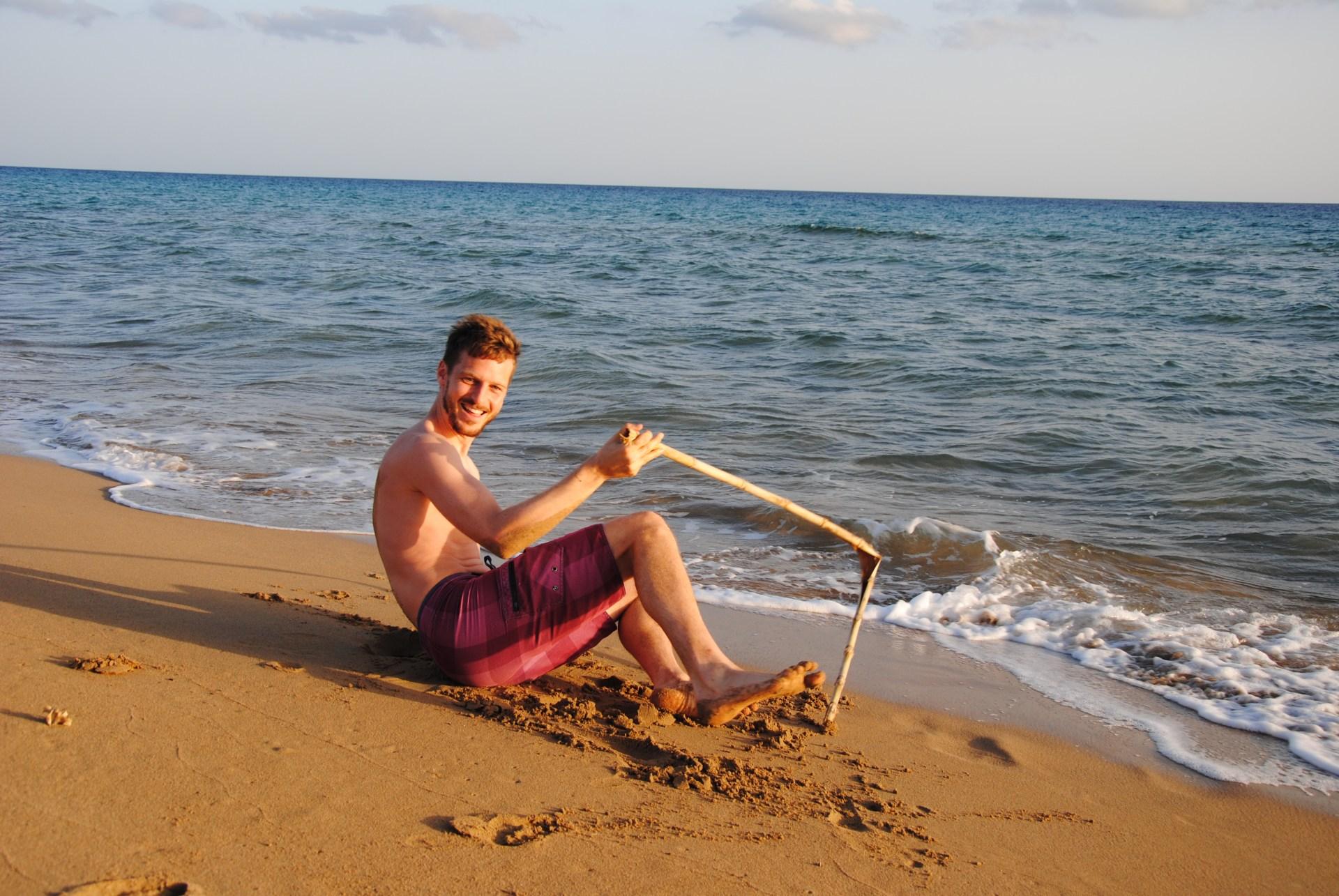 Sebastian liegt lachend am Strand und hält einen kaputten Stock