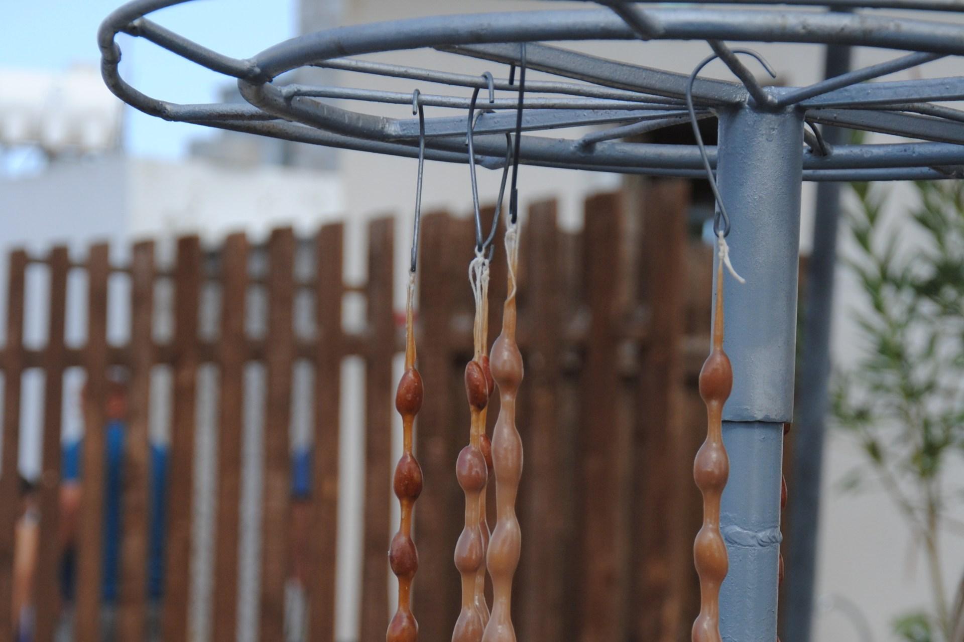 Mandeln in Johannisbrotsirup hängen an einem Gerüst