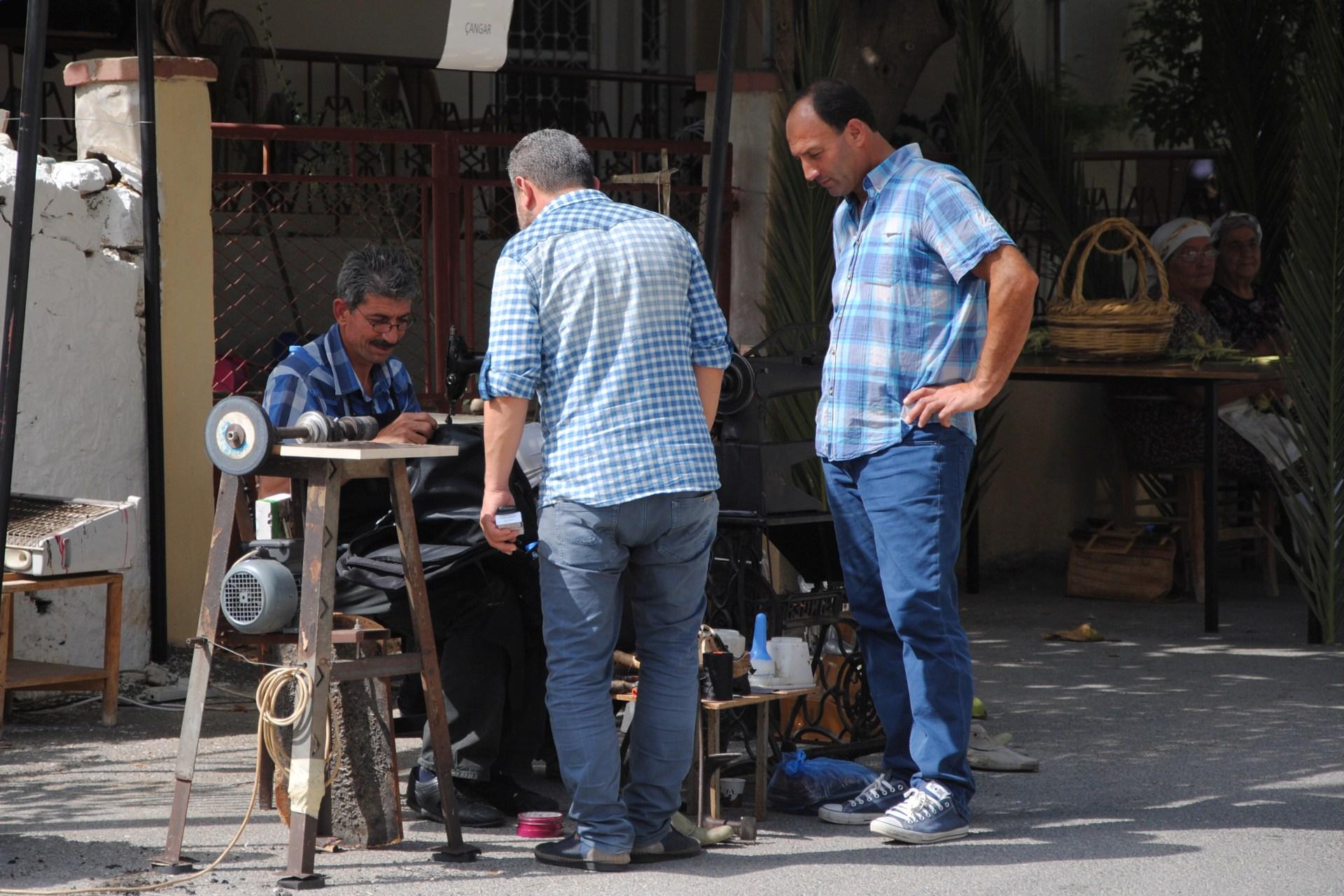Ein Schneider unterhält sich mit zwei Männern