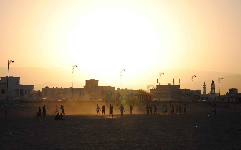 Menschen spielen im Abendlicht Fußball am Strand