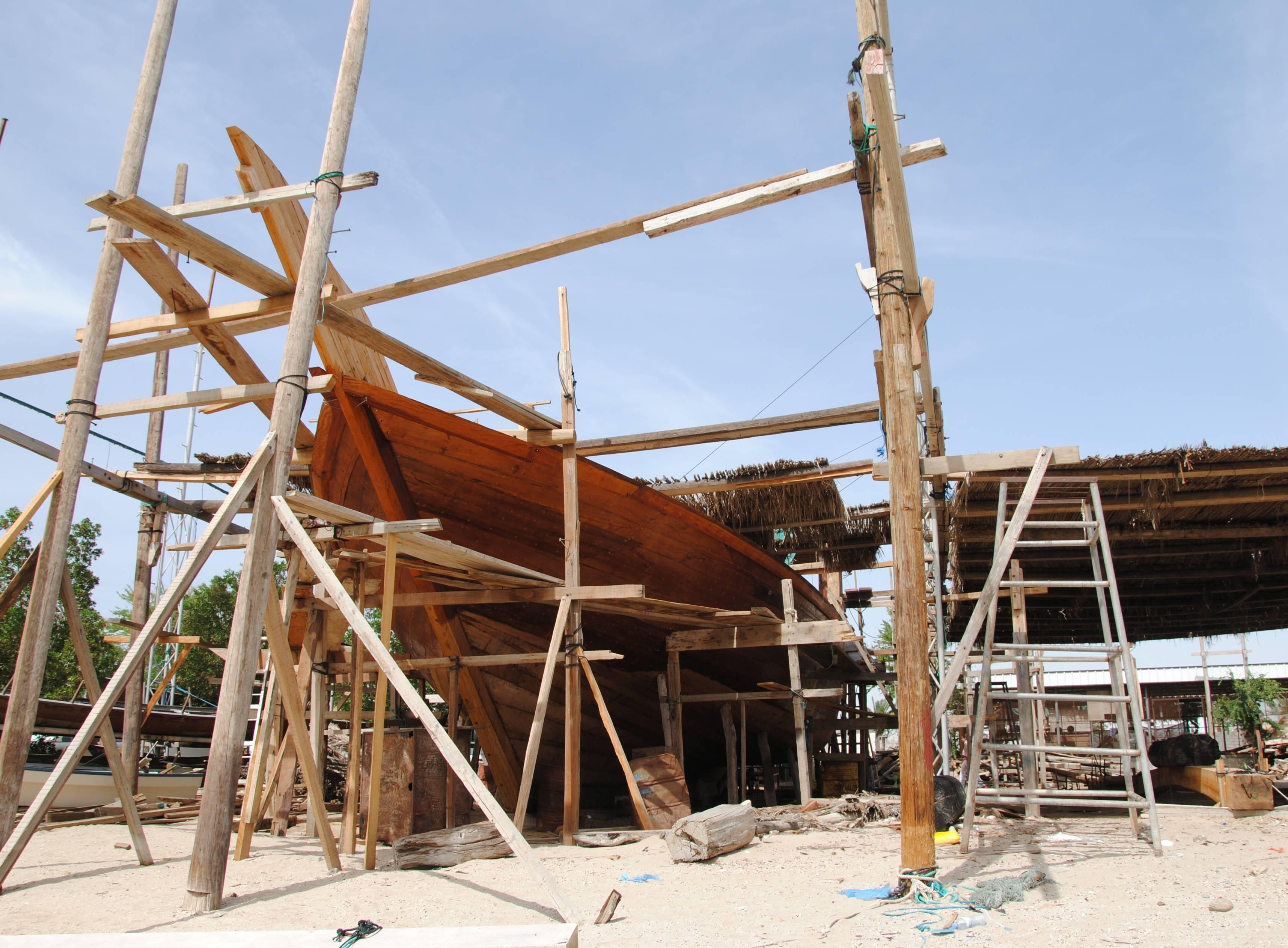 Dhau-Werft mit einem eingerüsteten Holzschiff