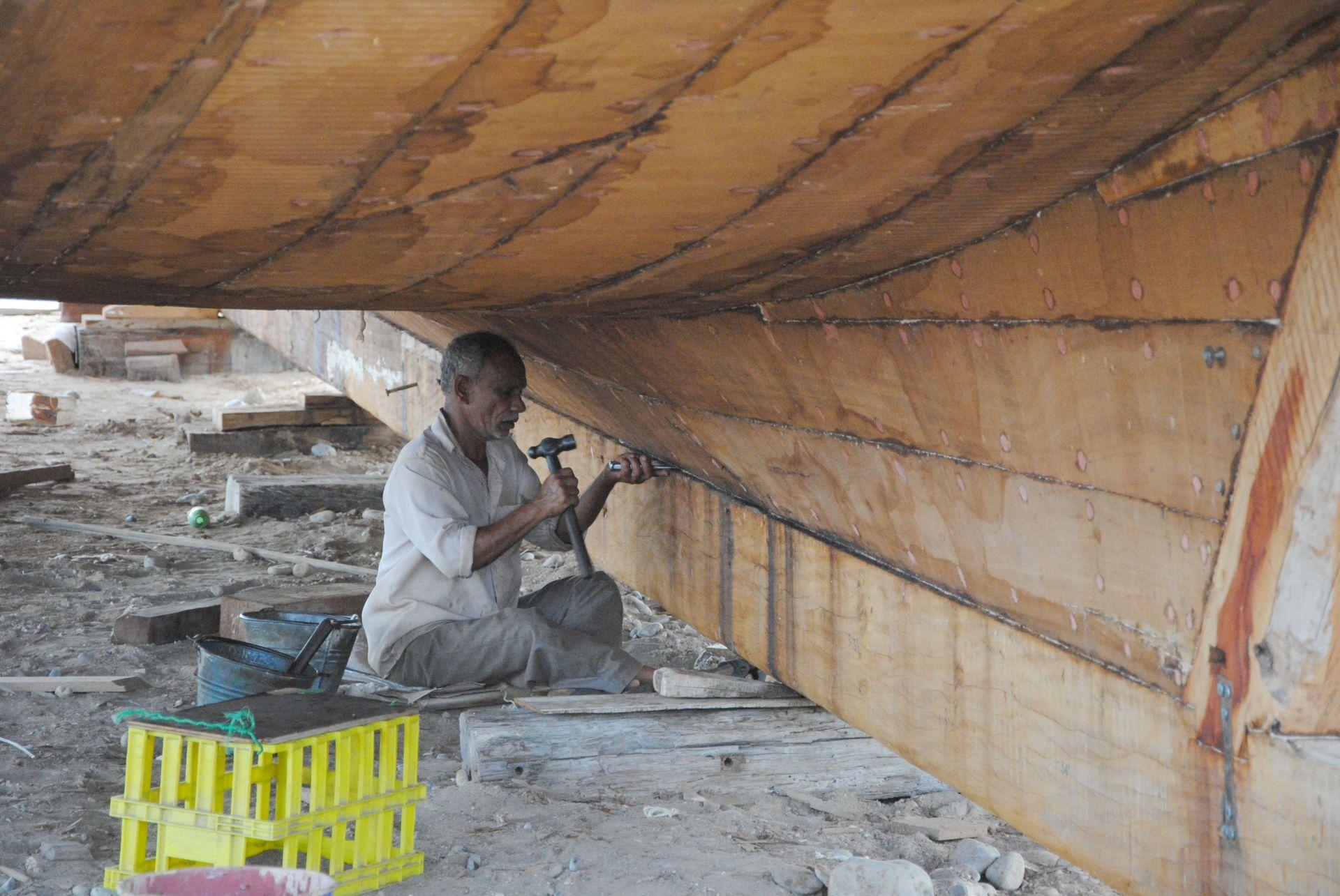 Ein Mann arbeitet am Kiel einer Dhau