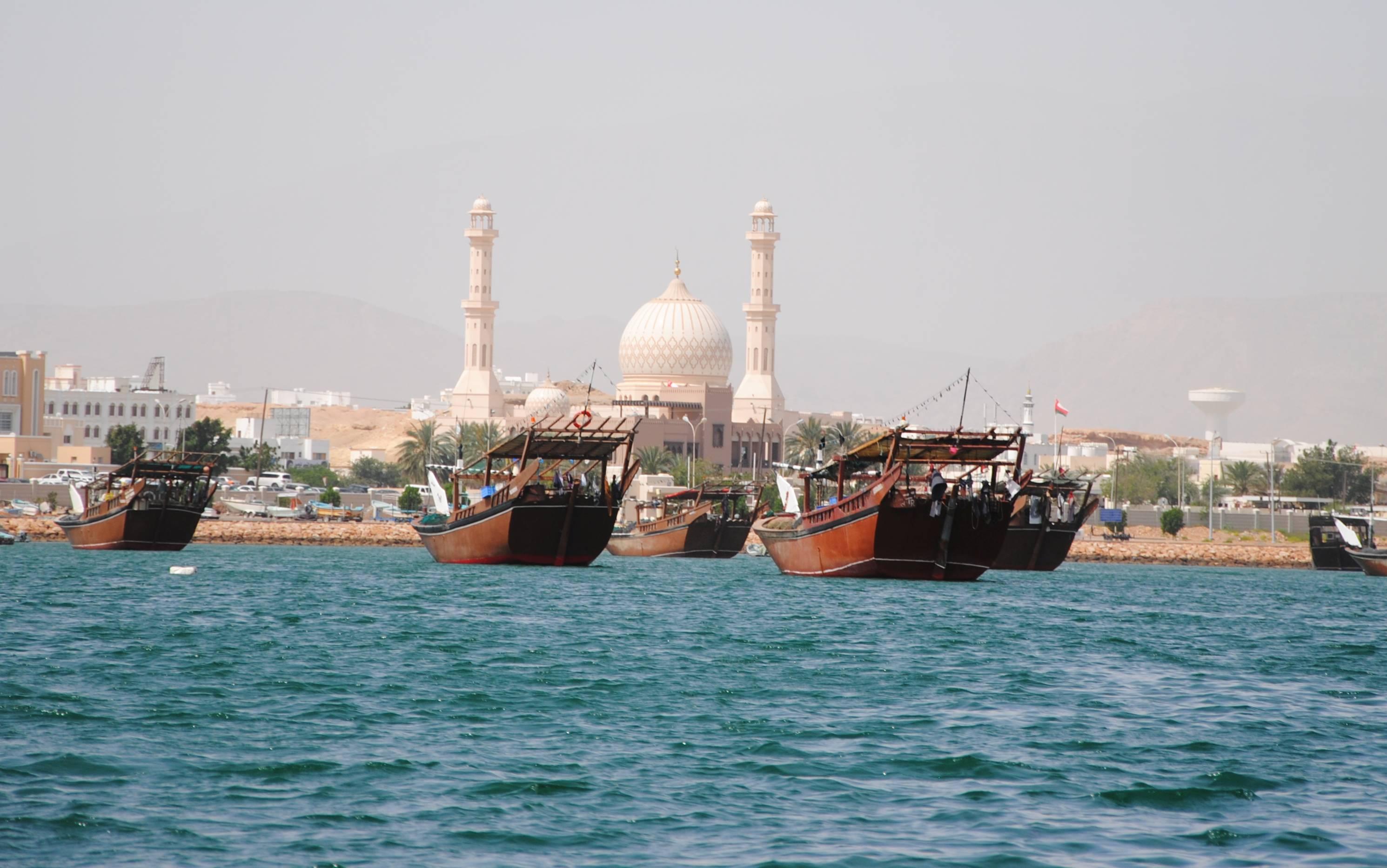 Dhaus im Hafen und eine Moschee im Hintergrund
