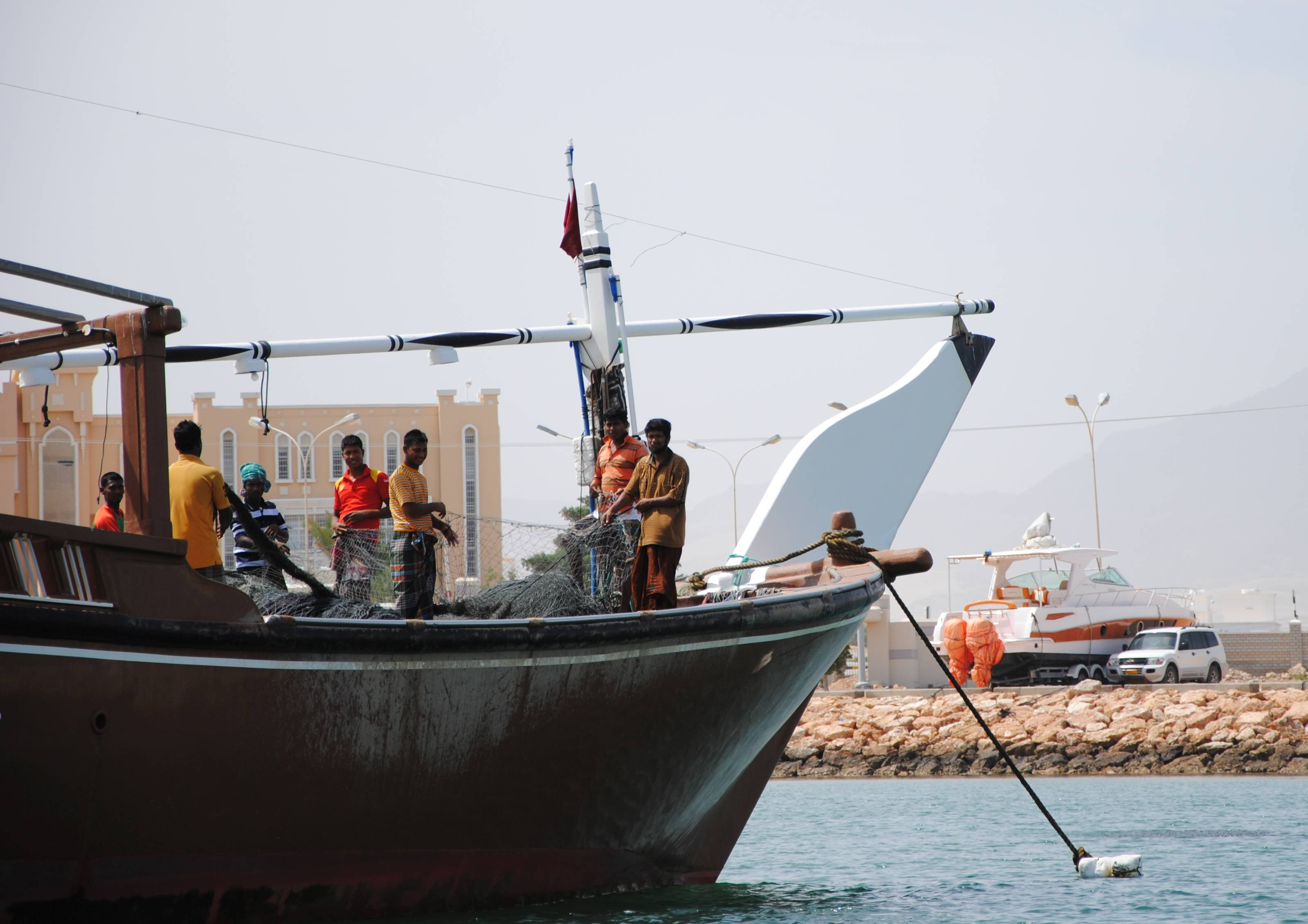 Fischer stehen auf einer Dhau und halten ein Fischernetz