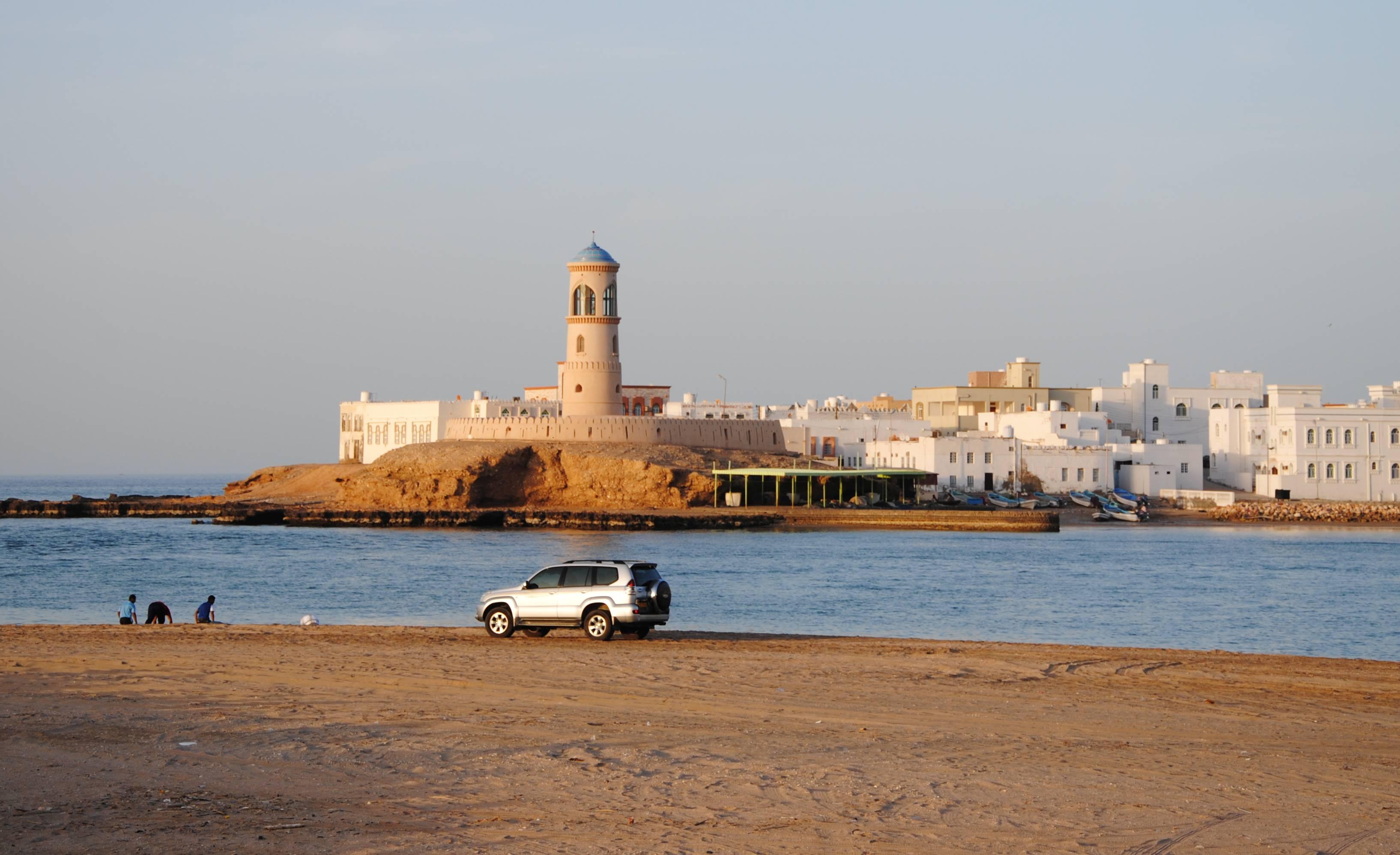 Ein Auto am Ufer vor einem Leuchtturm