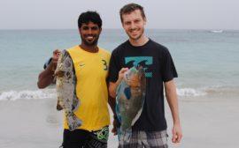 Sebastian steht mit einem Fischer am Meeresufer. Beide halten je einen Fisch in der Hand.