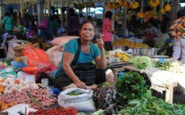 Eine rauchende Frau sitzt zwischen Gemüse auf dem Wochenmarkt