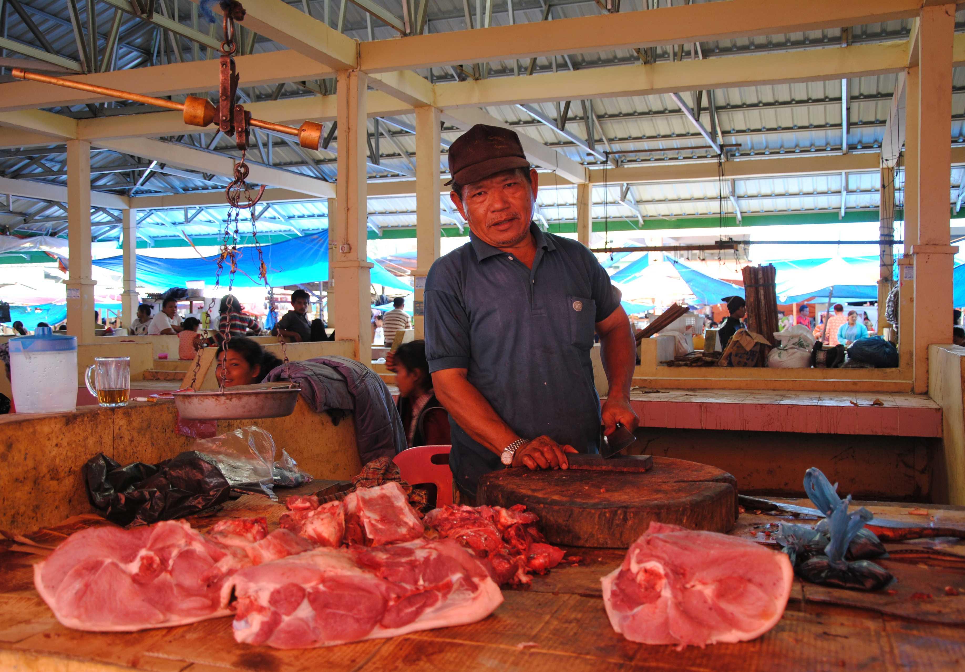 Ein Mann steht vor großen Fleischstücken