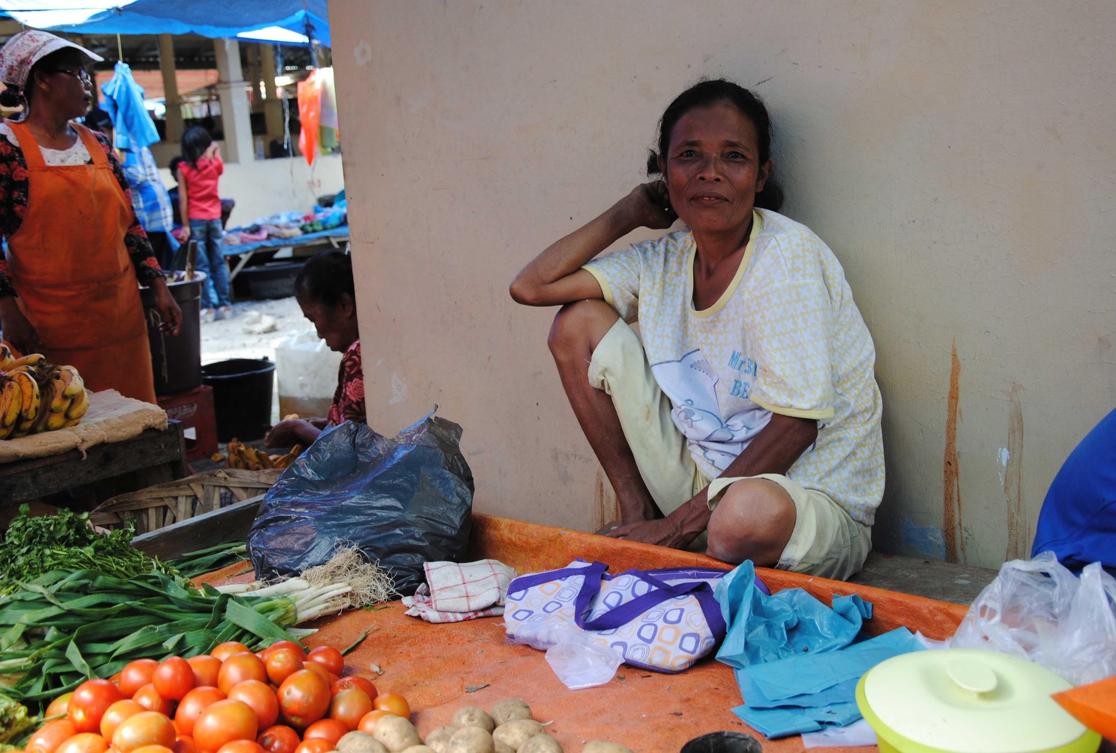 Eine Frau sitzt an einem Gemüsestand