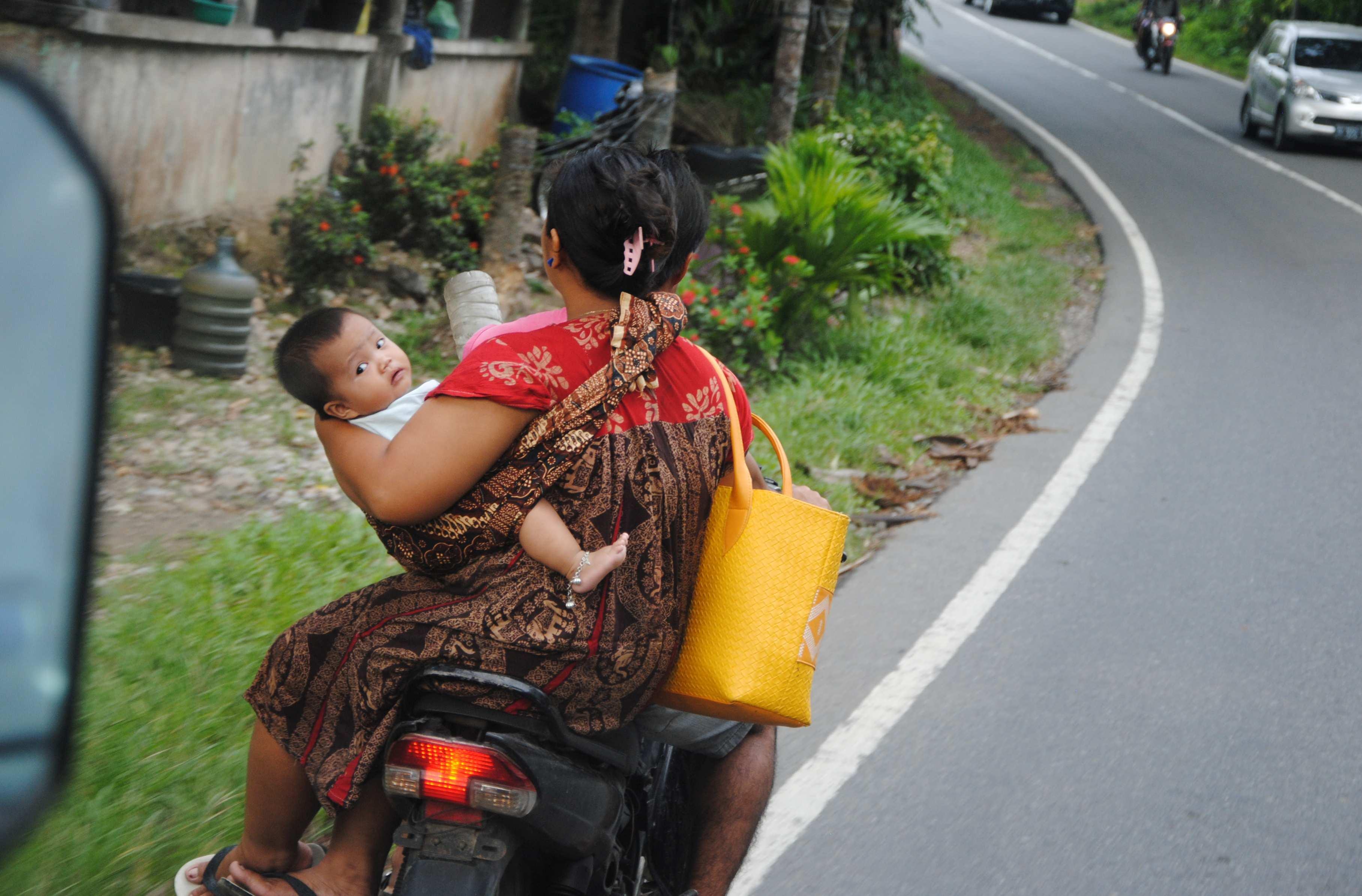 Eine Frau sitzt mit einem Kleinkind auf einem Motorrad
