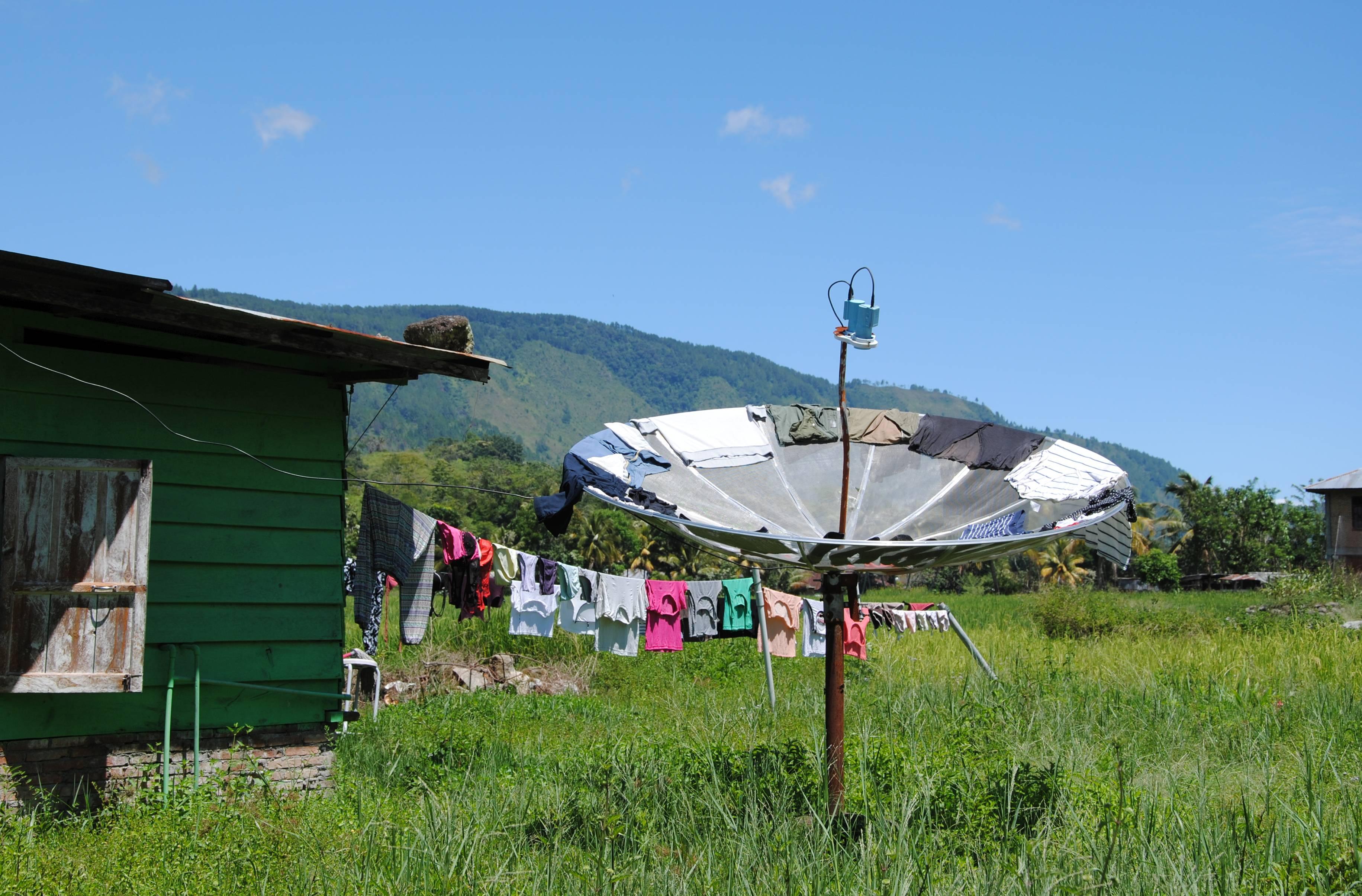 Eine Satelitenschüssel, auf der Wäsche zum Trocknen ausgelegt ist