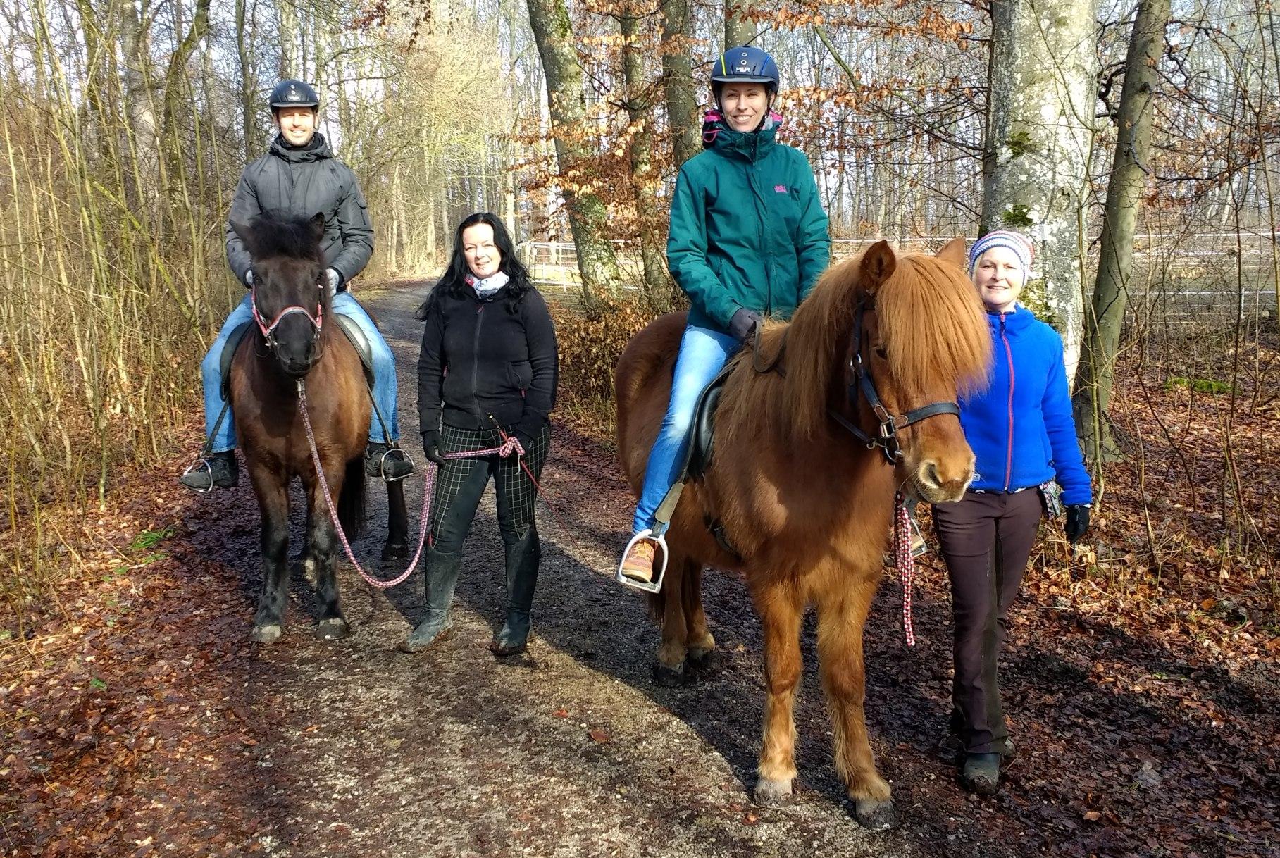 Leo und Sebastian sitzen auf Pferden und werden von zwei Frauen geführt