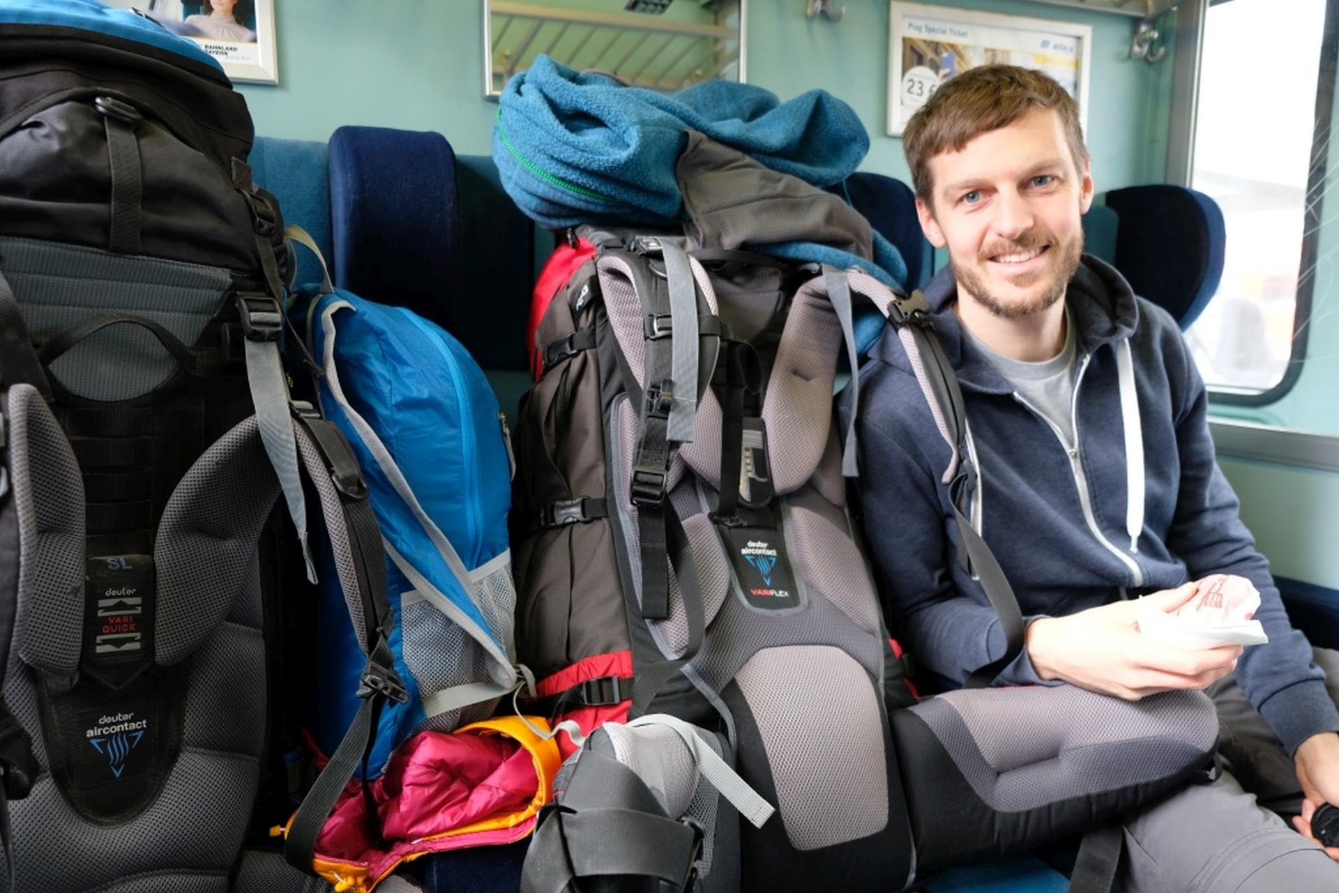 Sebastian sitzt neben zwei Reiserucksäcken im Zug