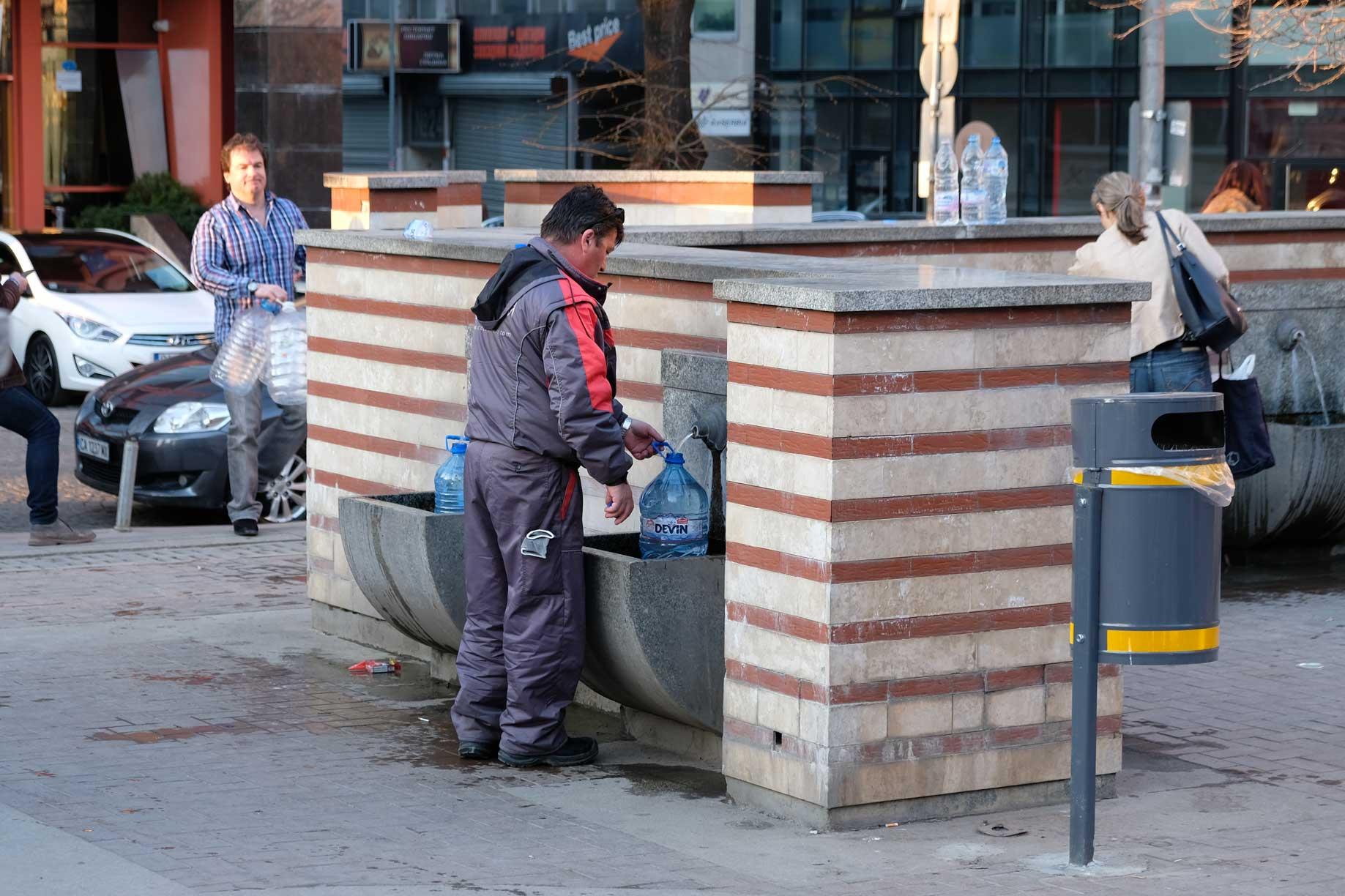 Ein Mann füllt Brunnenwasser in einen Kanister