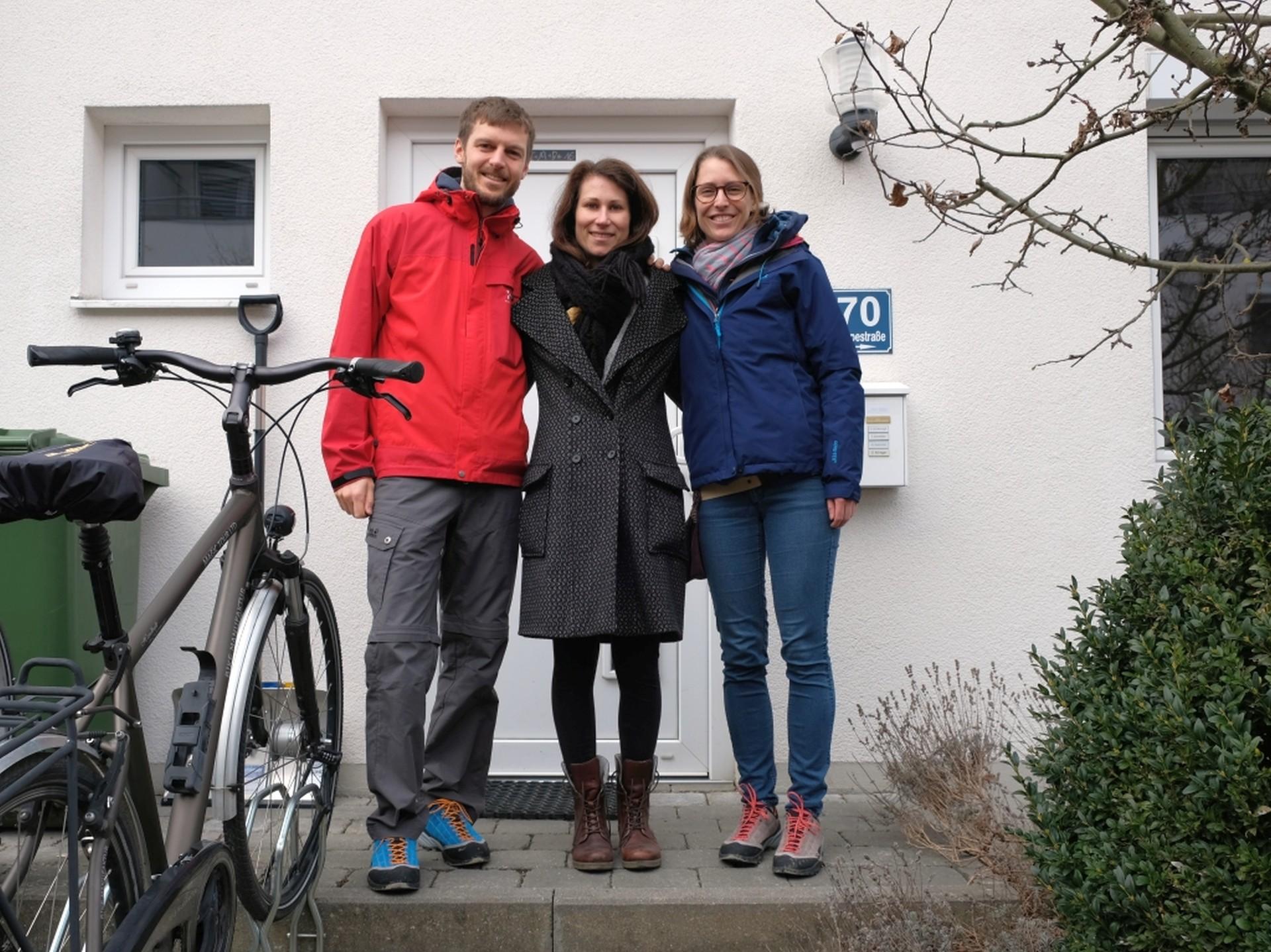 Sebastian, Jana und Leo stehen vor einem Haus