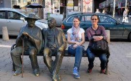 Leo und Hristina sitzen neben zwei Statuen auf einer Bank