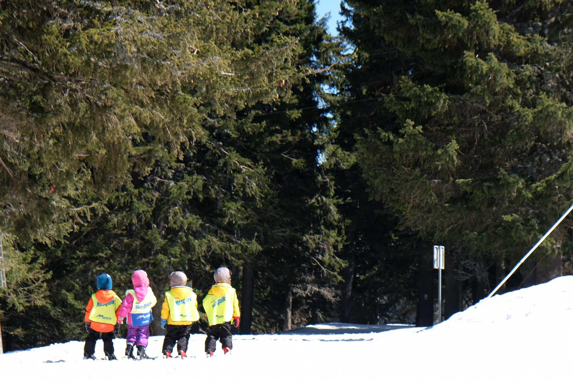 Vier Kinder auf Skiern im Schnee