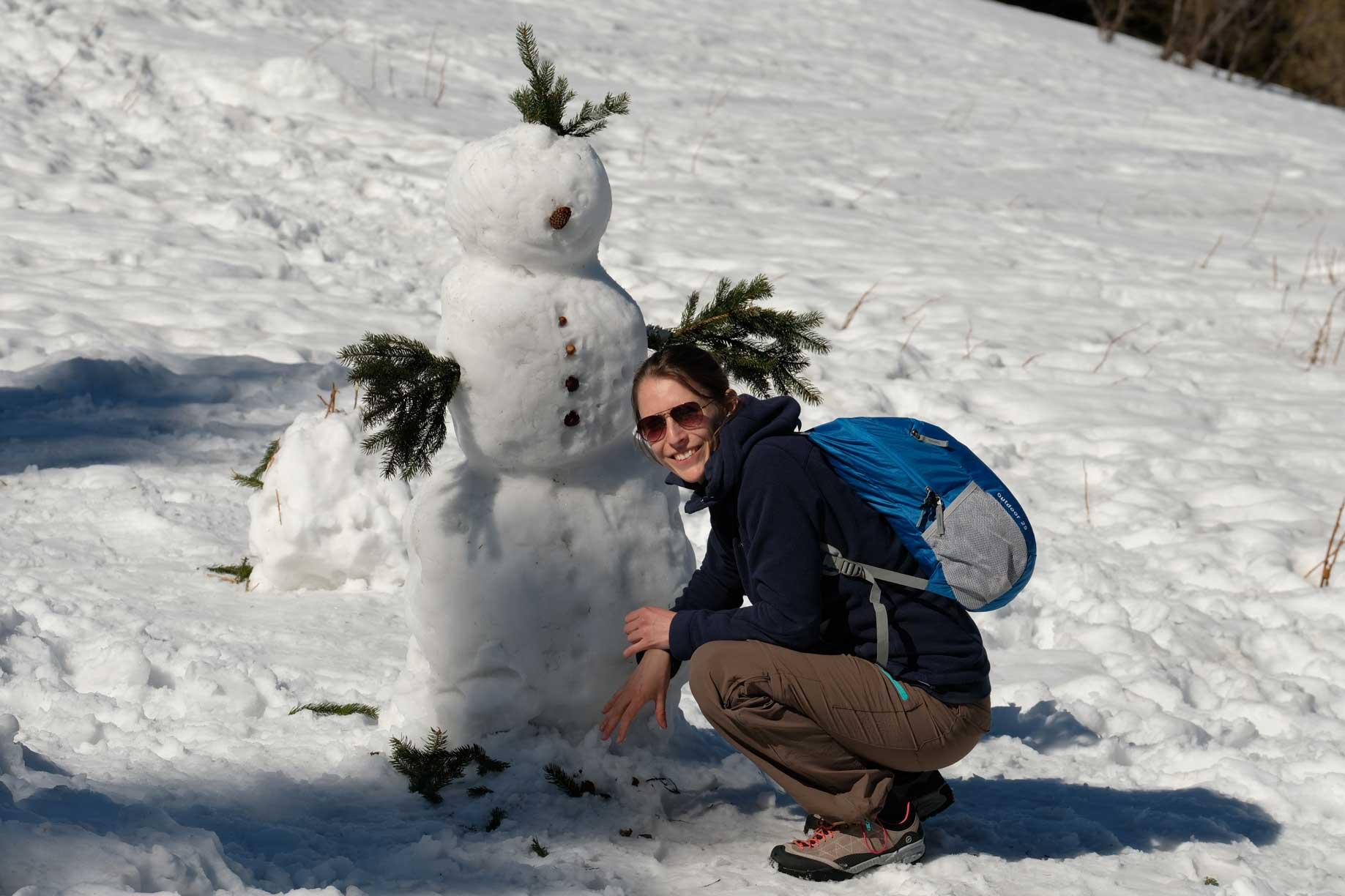 Leo in der Hocke vor einem Schneemann