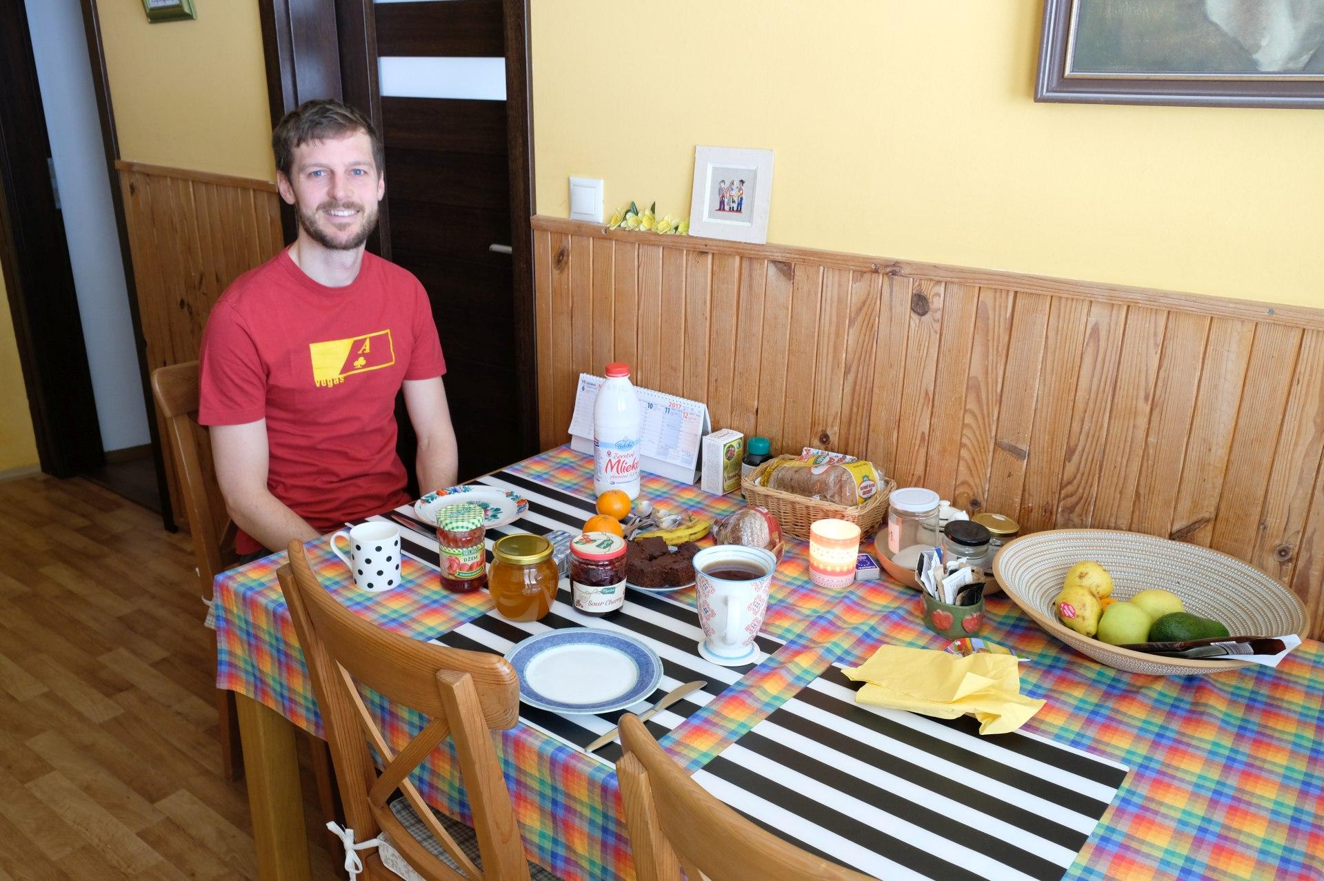 Sebastian sitzt an einem Frühstückstisch