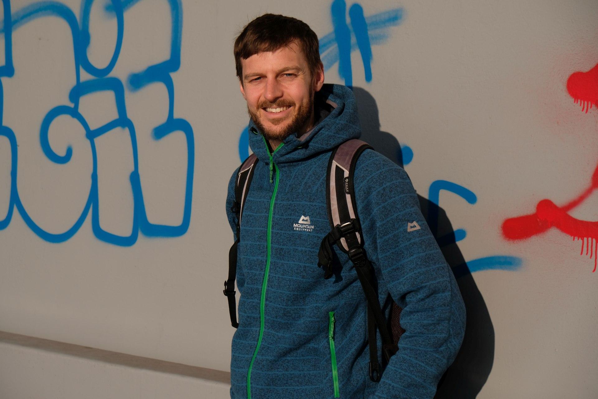 Sebastian vor einer mit Graffiti besprühten Mauer