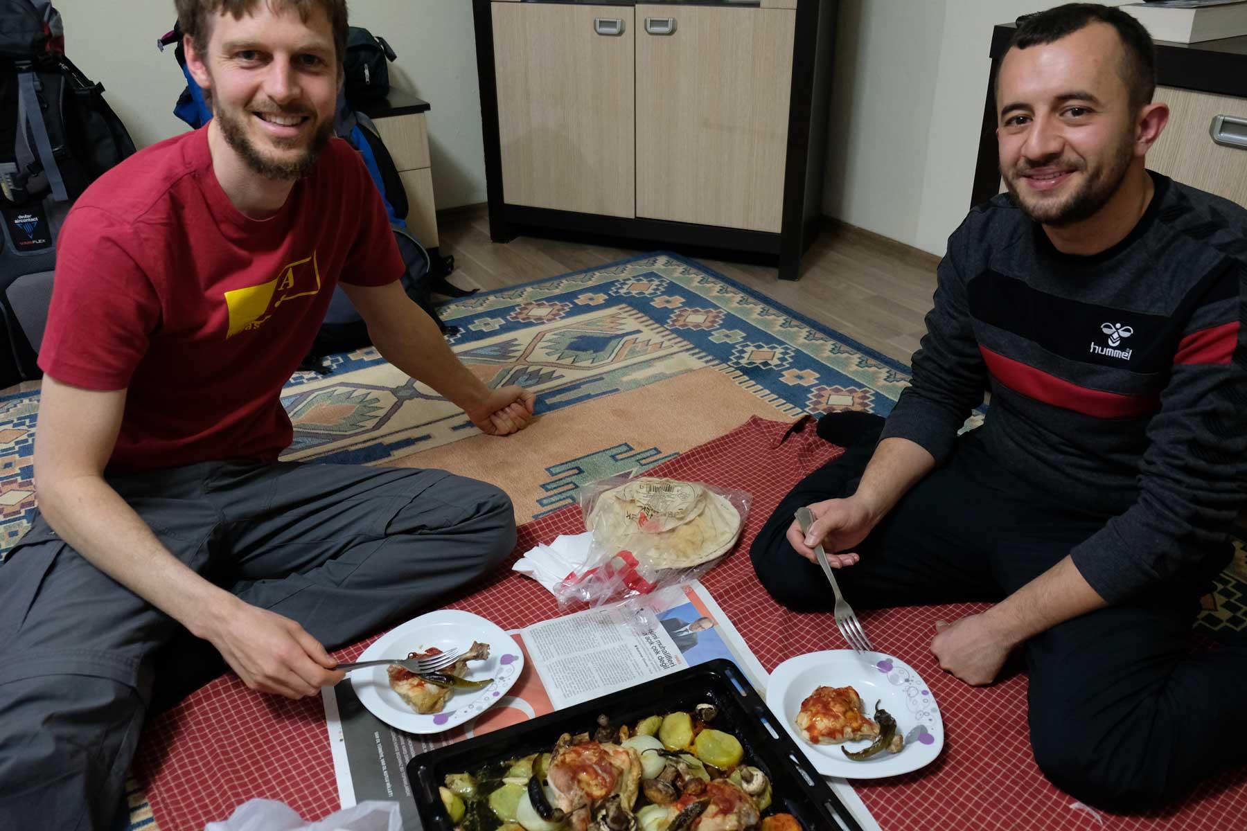 Sebastian und Fatih sitzen auf dem Boden und essen