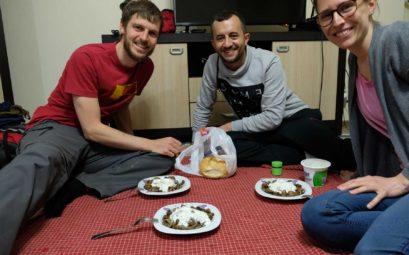 Sebastian und Leo sitzen mit Fatih auf dem Boden und essen