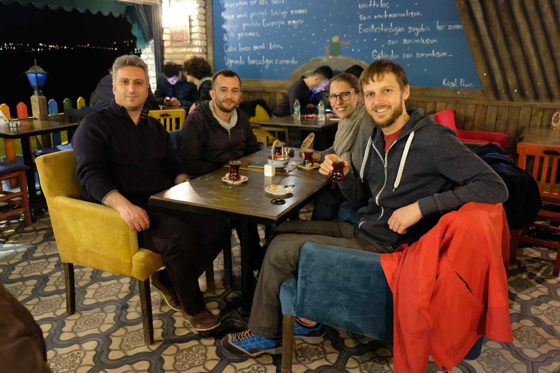 Çan, Fatih, Leo und Sebastian sitzen an einem Tisch und trinken türkischen Tee