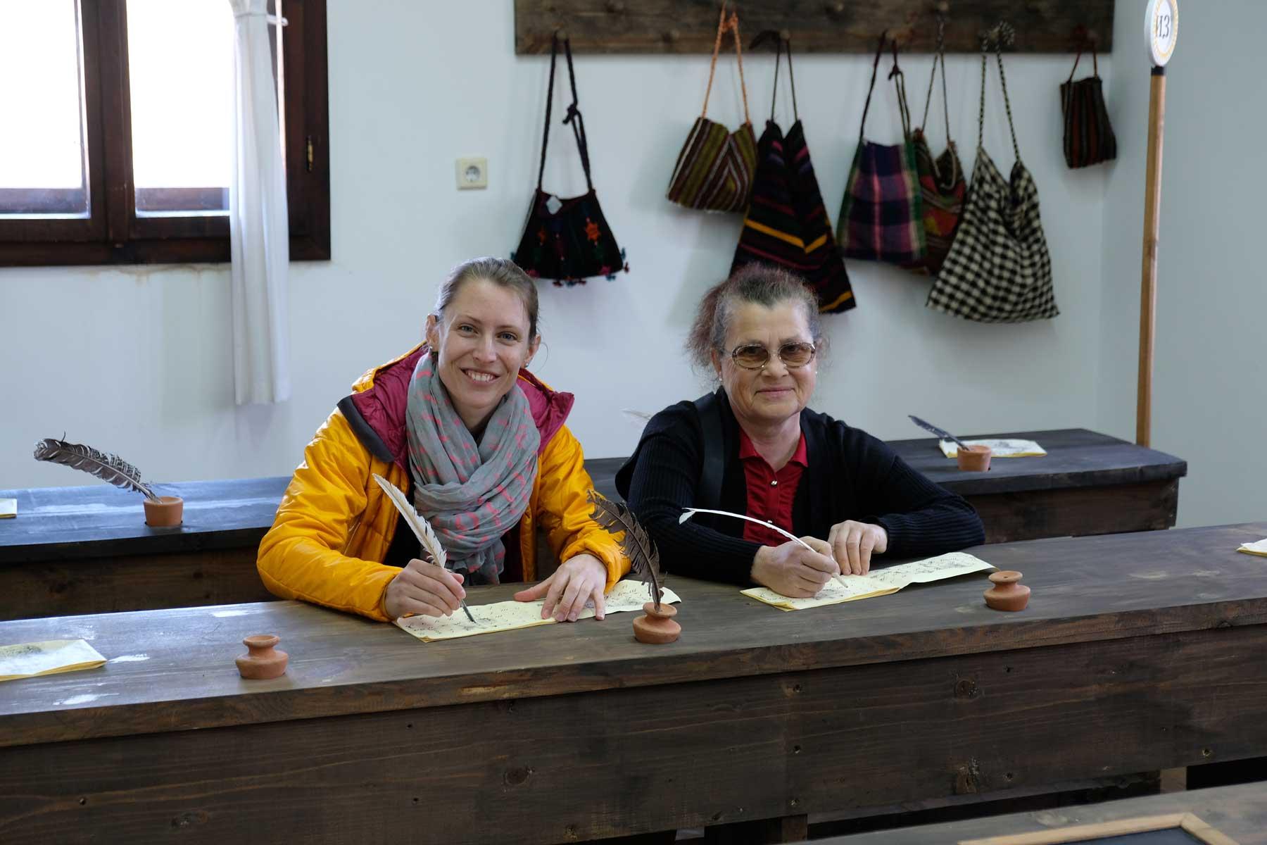 Leo und Petranka sitzen an einer Schulbank und halten eine Schreibfeder in der Hand