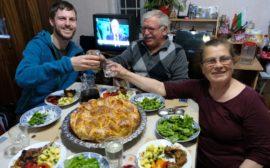 Sebastian, Georgi und Petranka sitzen an einem reich gedeckten Tisch und prosten sich zu